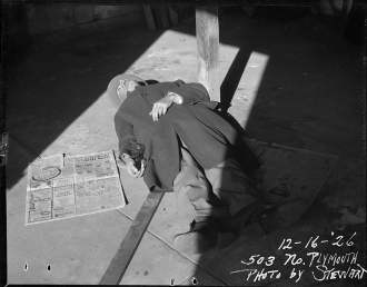 Dead body laying on the ground with gun at side – 1926