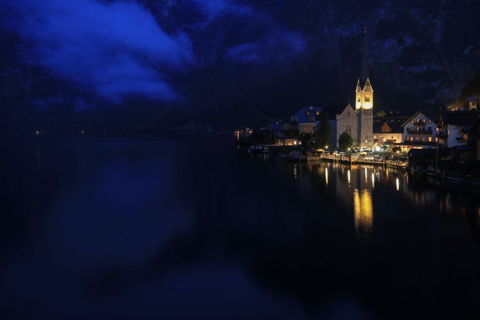 The alpine village of Hallstatt glows at dusk on the banks of Hallstaettersee lake in Hallstatt